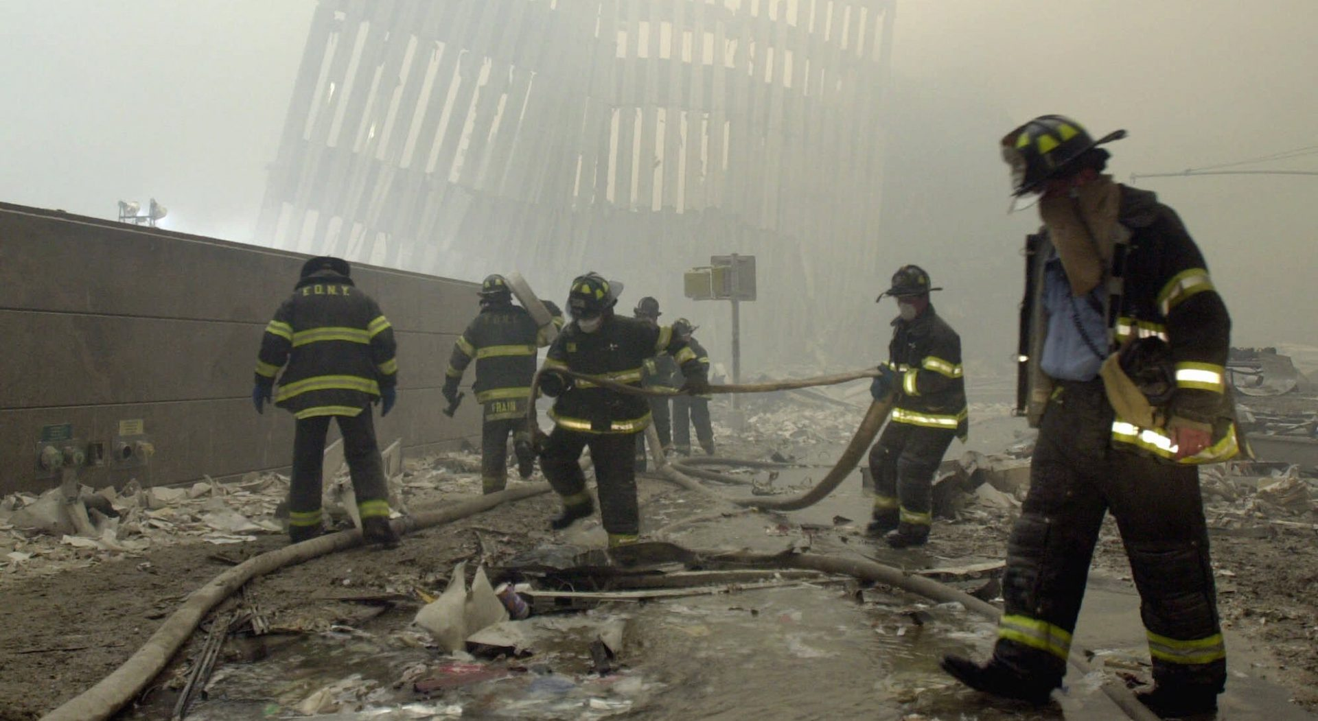 In this Sept. 11, 2001 file photo, with the skeleton of the World Trade Center twin towers in the background, New York City firefighters work amid debris on Cortlandt St. after the terrorist attacks.