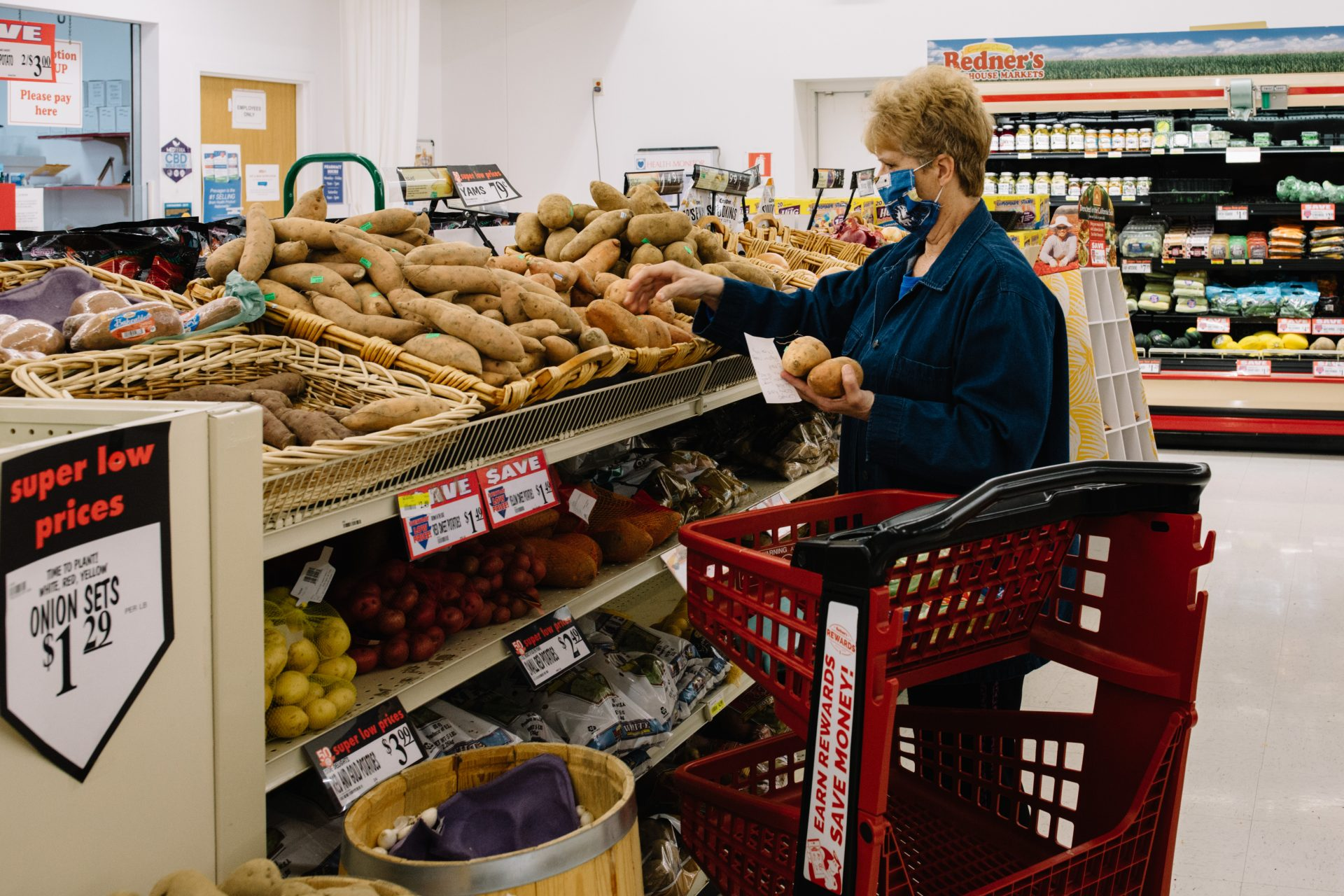 A shopper wearing a fabric mask picks out potatoes at the grocery store on April 10, 2020.