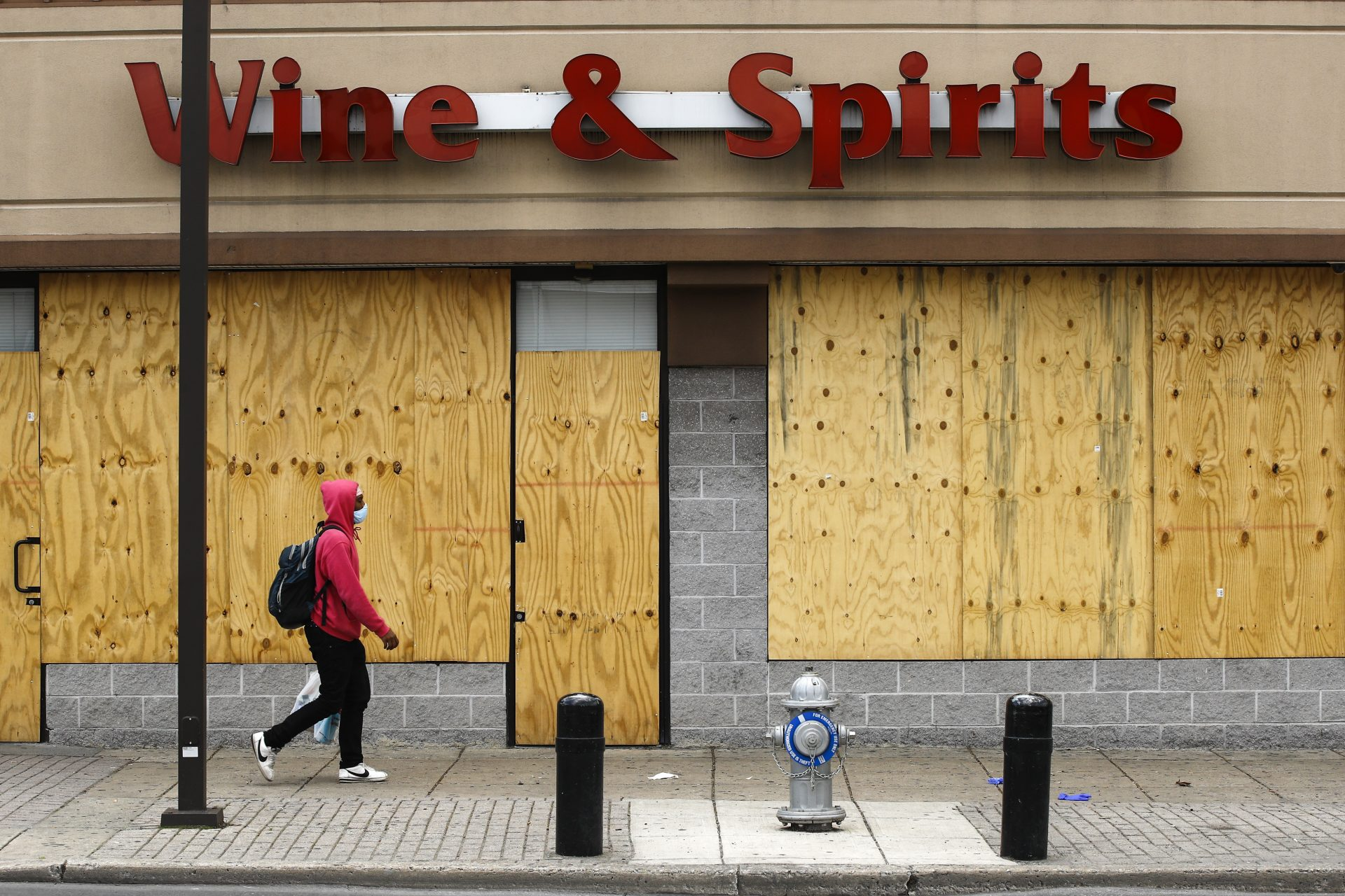 A person wearing a protective face mask as a precaution against the coronavirus walks past a boarded up Wine and Spirits store in Philadelphia, Thursday, April 16, 2020. Pennsylvania's liquor agency says workers are coming back on the job at more than 100 shuttered state-owned liquor stores to help process online orders.