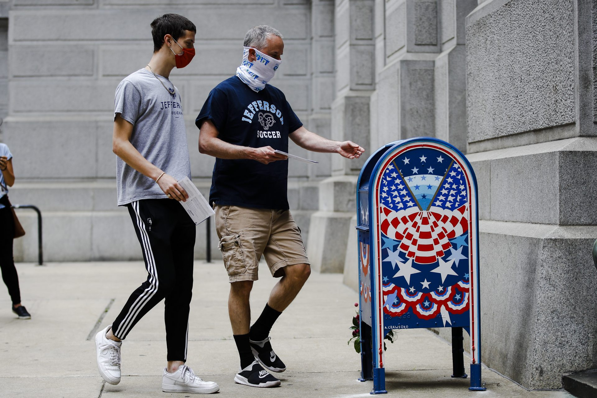 Benjamin Graff, center, and his son Jacob Graff, 19, drop off their mail-in ballots for the Pennsylvania primary election, in Philadelphia, Tuesday, June 2, 2020. (AP Photo/Matt Rourke)