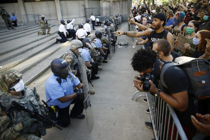 Philadelphia police and National Guard take a knee at the suggestion of Philadelphia Police Deputy Commissioner Melvin Singleton, unseen, outside Philadelphia Police headquarters in Philadelphia, Monday, June 1, 2020 during a march calling for justice over the death of George Floyd, Floyd died after being restrained by Minneapolis police officers on May 25.