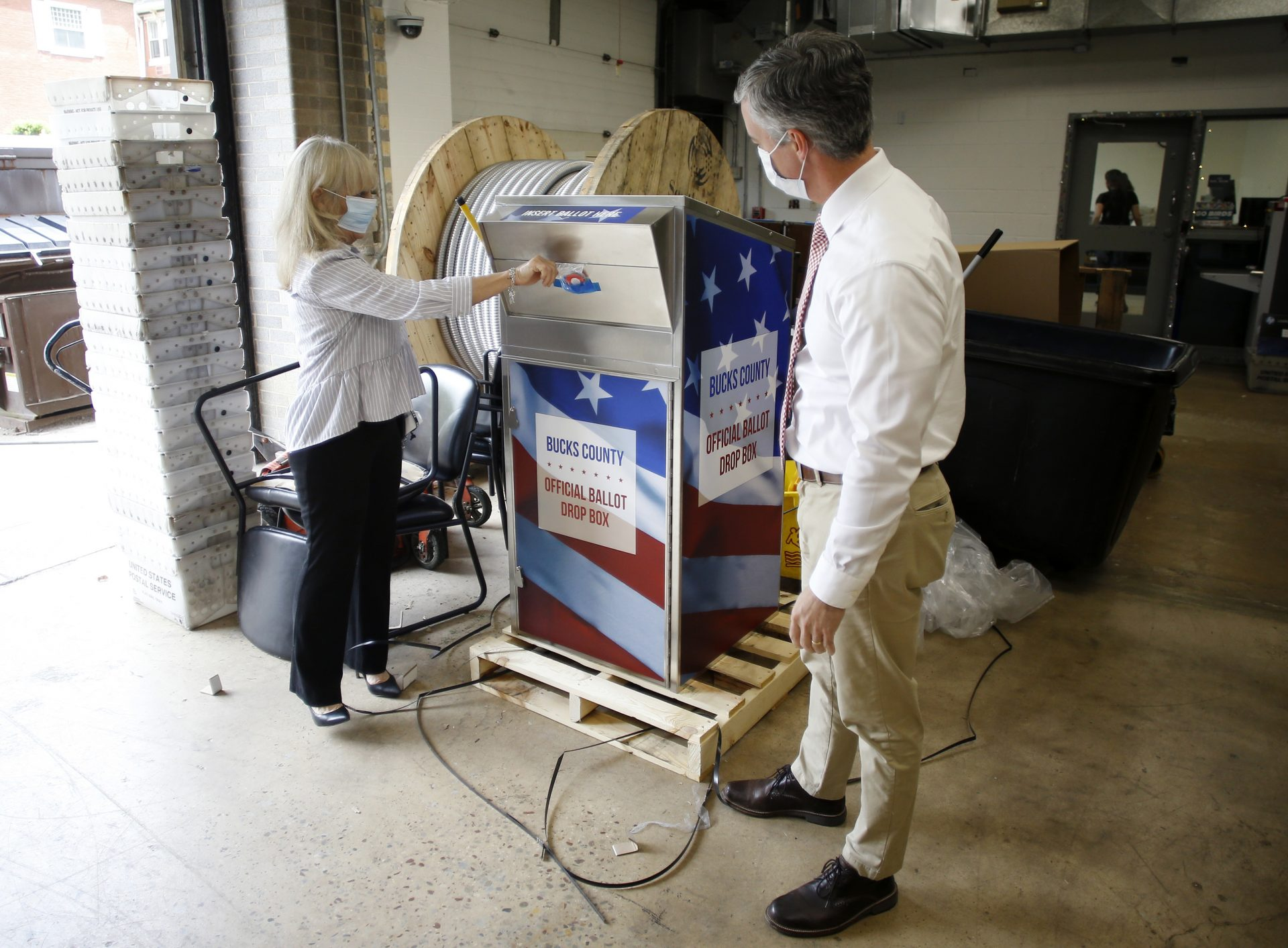 FILE PHOTO: In this May 27, 2020, photo, Bucks County commissioners Diane Ellis-Marseglia, left, and Robert Harvie unpack a new ballot drop box at the county's administration building prior to the primary election in Doylestown, Pa.