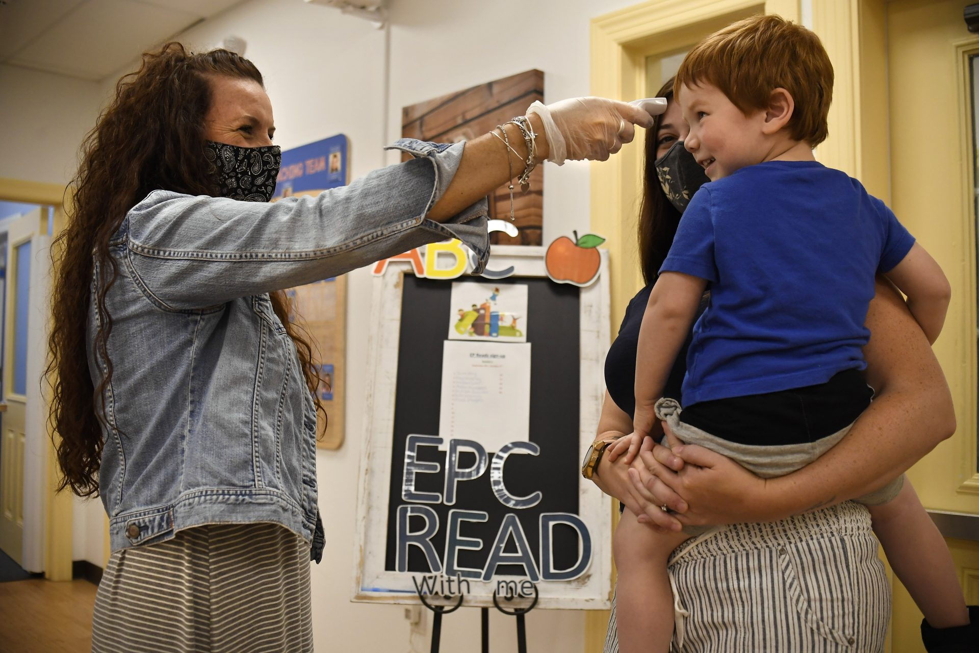 In this Thursday Aug. 27, 2020 photo, Assistant Director Tammy Cavanaugh, left, takes the temperature of Maverick Barbera has he is held by his mother Katrina Meli at Educational Playcare, in Glastonbury, Conn. All children entering the daycare have their temperature taken.