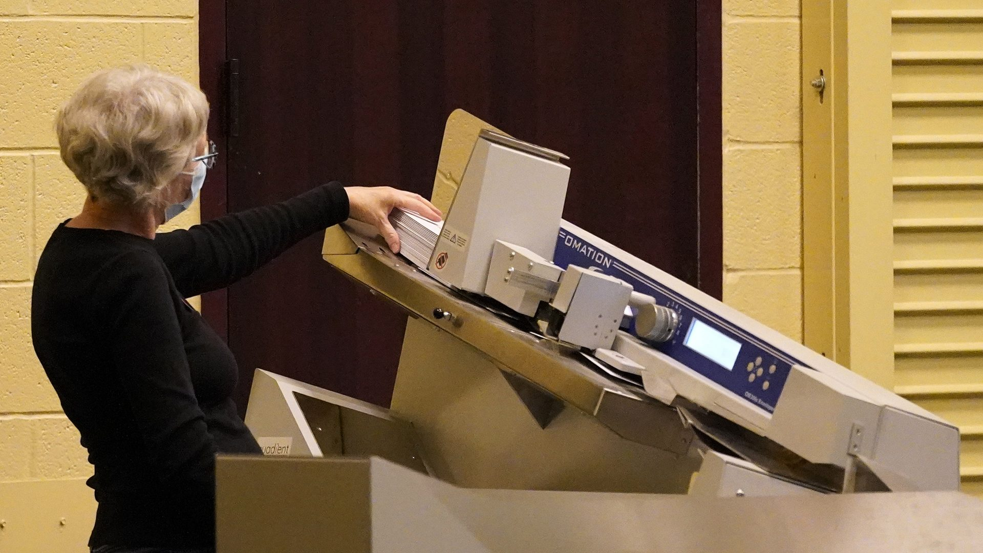 A worker scans mail-in ballots through a counting machine before they are counted, Wednesday, Nov. 4, 2020, at the convention center in Lancaster, Pa., following Tuesday's election.