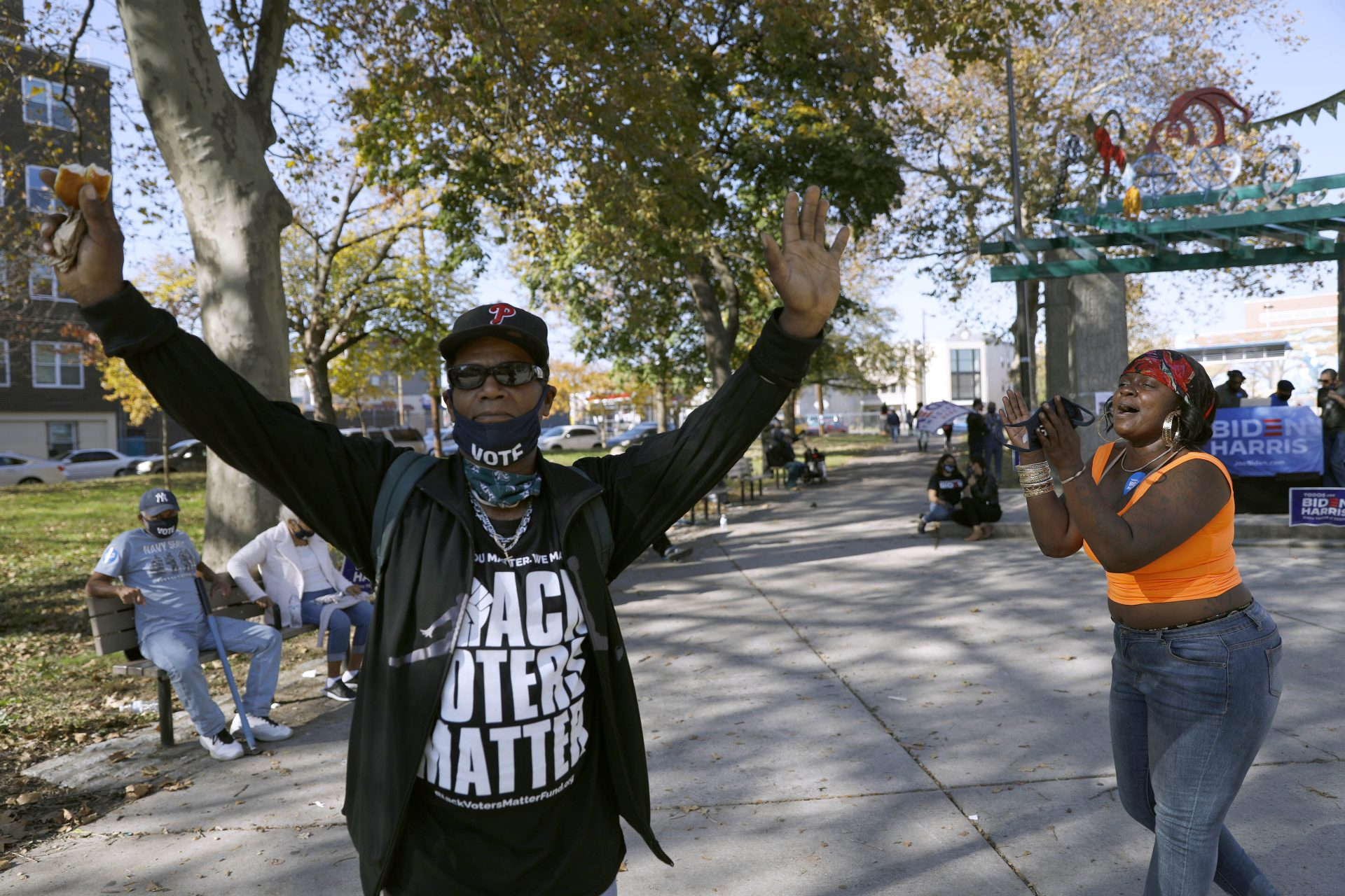 """A man wears a shirt that says, """"Black voters matter,"""" while dancing, Sunday, Nov. 8, 2020, in Fairhill Suare Park in Philadelphia, to celebrate after Democrat Joe Biden defeated President Donald Trump to become 46th president of the United States."""