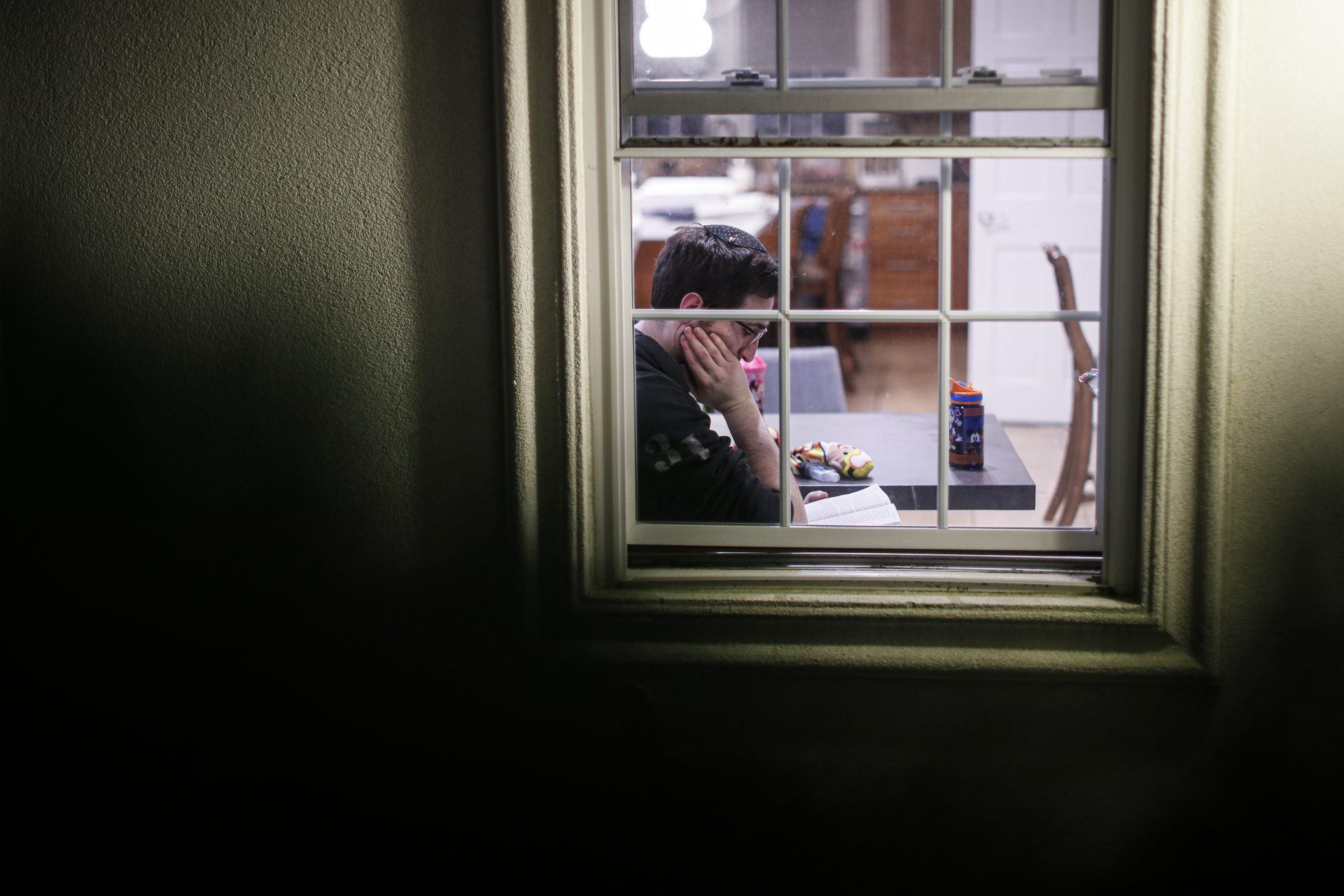 FILE PHOTO: A self-quarantined resident who says he tested positive for COVID-19 listens beside his window as volunteers perform a Purim reading from the Book of Esther, Monday, March 9, 2020, in New Rochelle, N.Y.