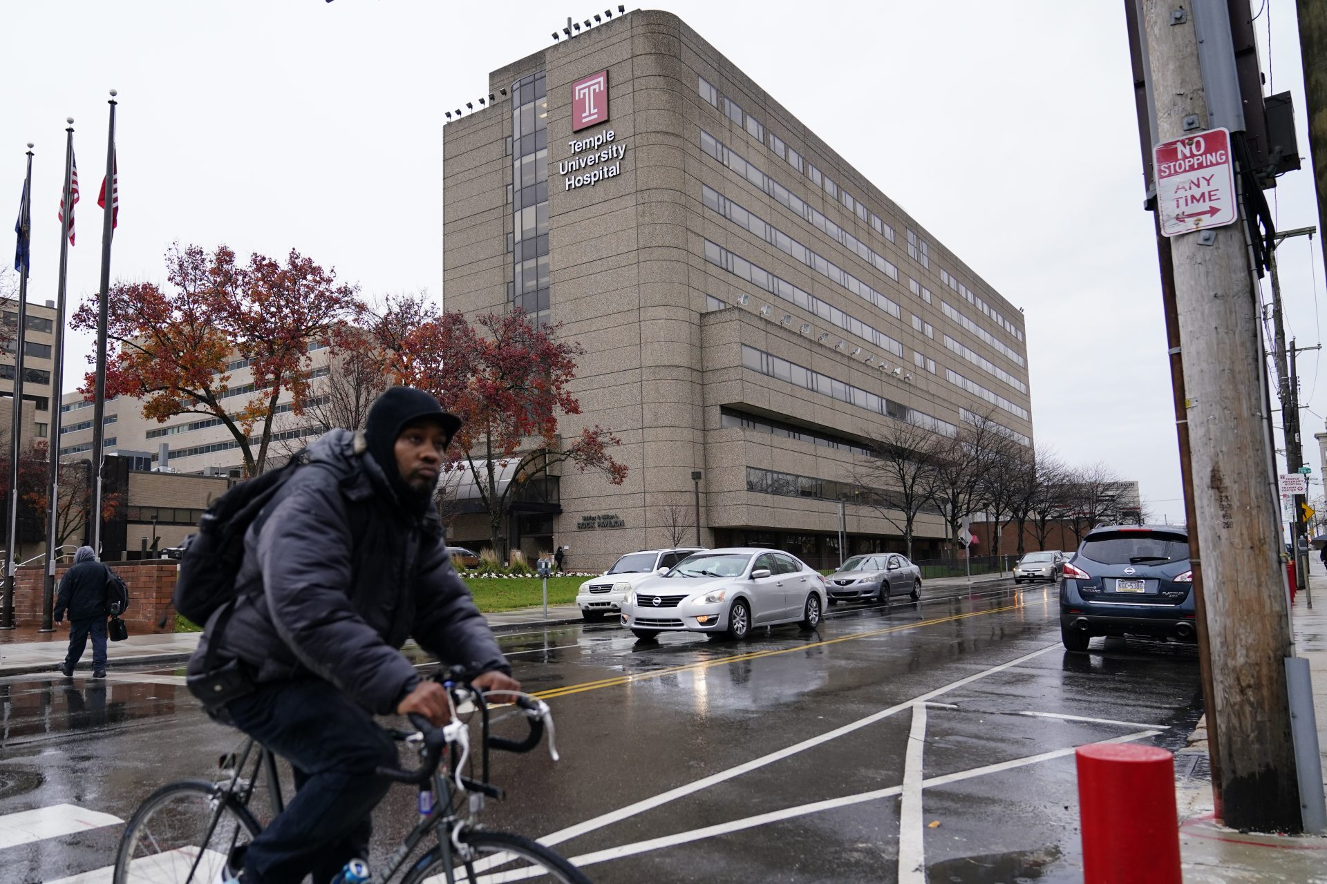 A man rides a bicycle past Temple University Hospital, Friday, Dec. 4, 2020, in Philadelphia. Hospital beds are filling up and medical staffs are being stretched to the limit as Pennsylvania's health care system copes with a growing number of seriously ill COVID-19 patients.