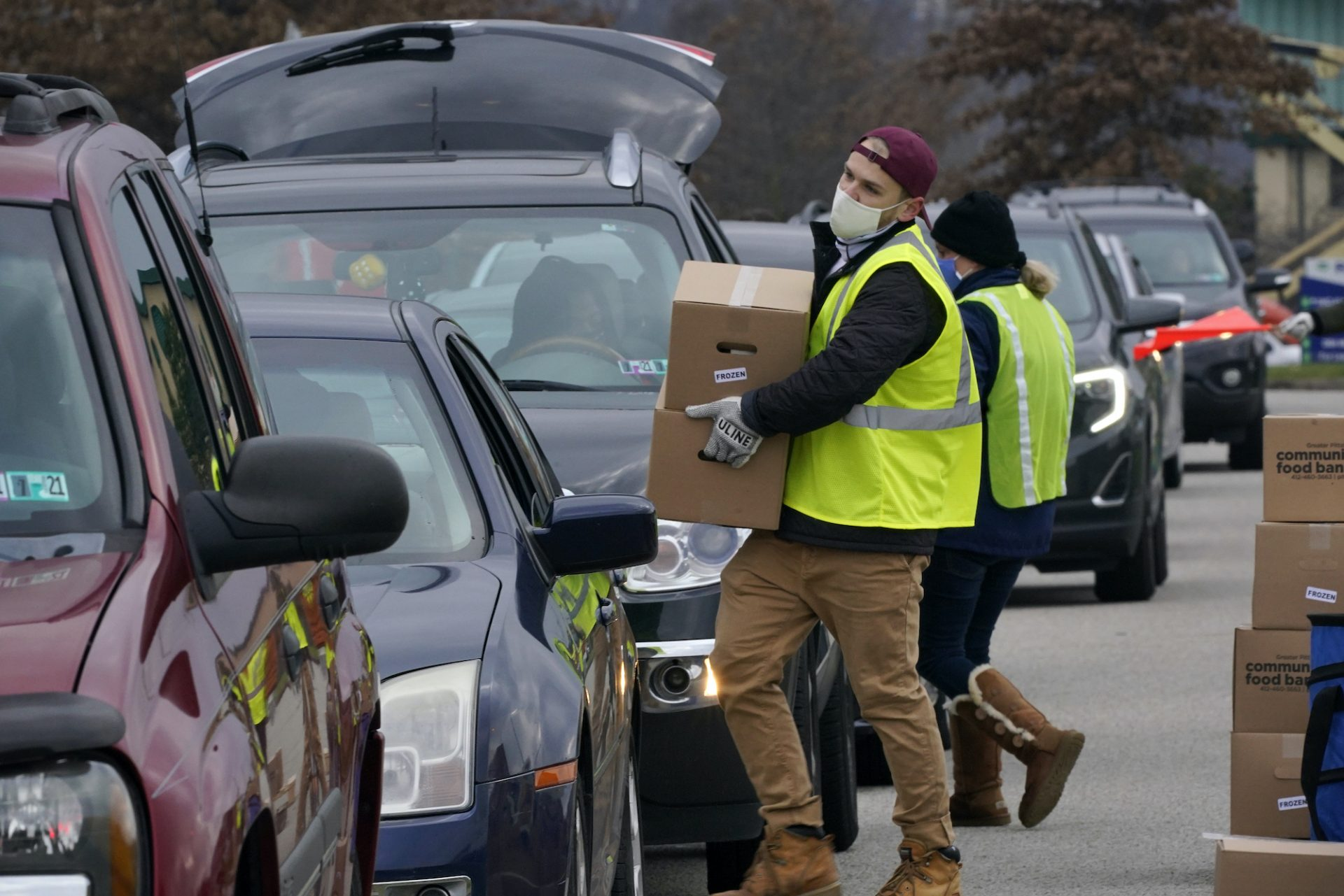 Volunteers load boxes of food into a car during a Greater Pittsburgh Community Food bank drive-up food distribution in Duquesne, Pa., Monday, Nov. 23, 2020.