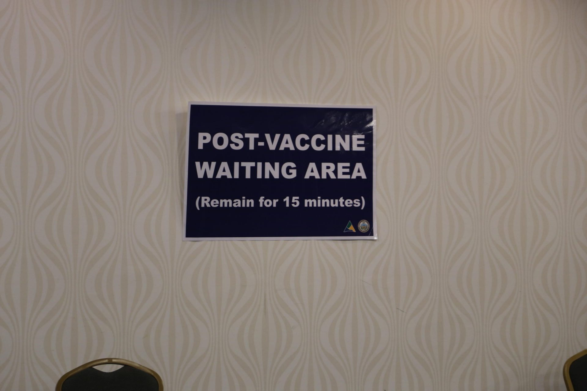 A sign marks the waiting area for people who received a COVID-19 vaccine. The 15-minute waiting period is a precaution because some people who received initial doses of the vaccine developed allergic reactions.