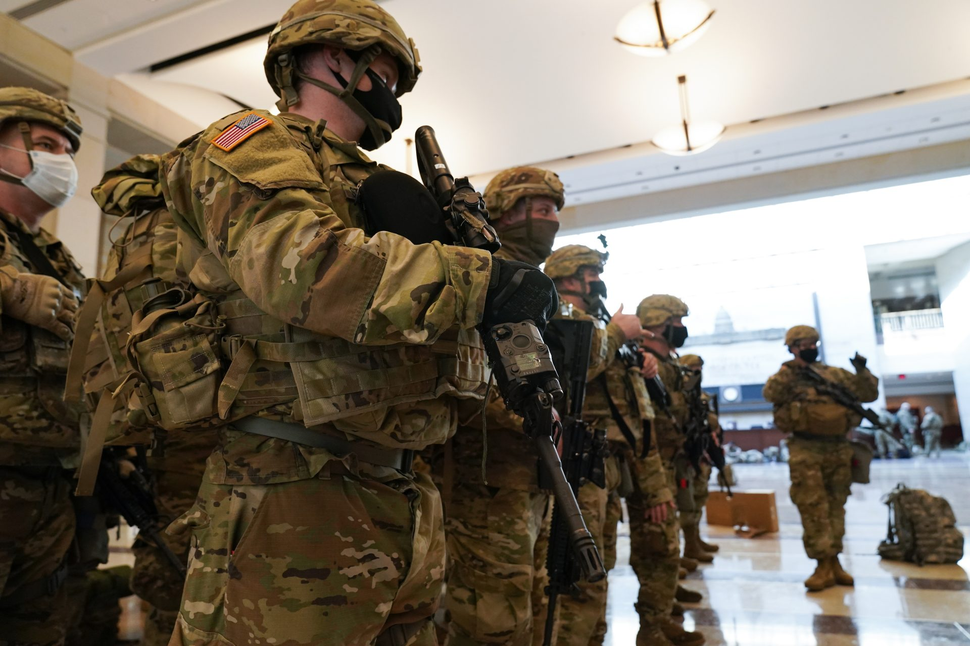 Troops stand in formation inside the Capitol Visitor's Center to reinforce security at the Capitol in Washington, Wednesday, Jan. 13, 2021. The House of Representatives is pursuing an article of impeachment against President Donald Trump for his role in inciting an angry mob to storm the Capitol last week.