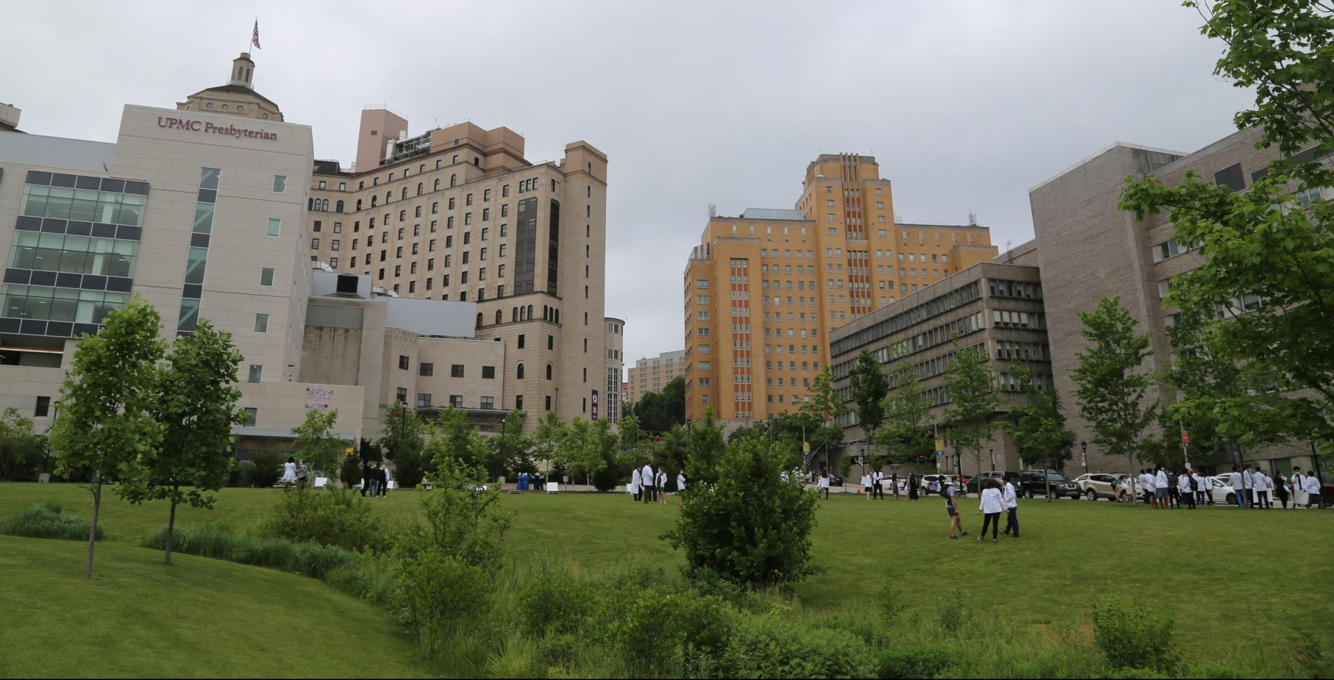 Health care workers socialize on the lawn outside UPMC Presbyterian Hospital in Pittsburgh.