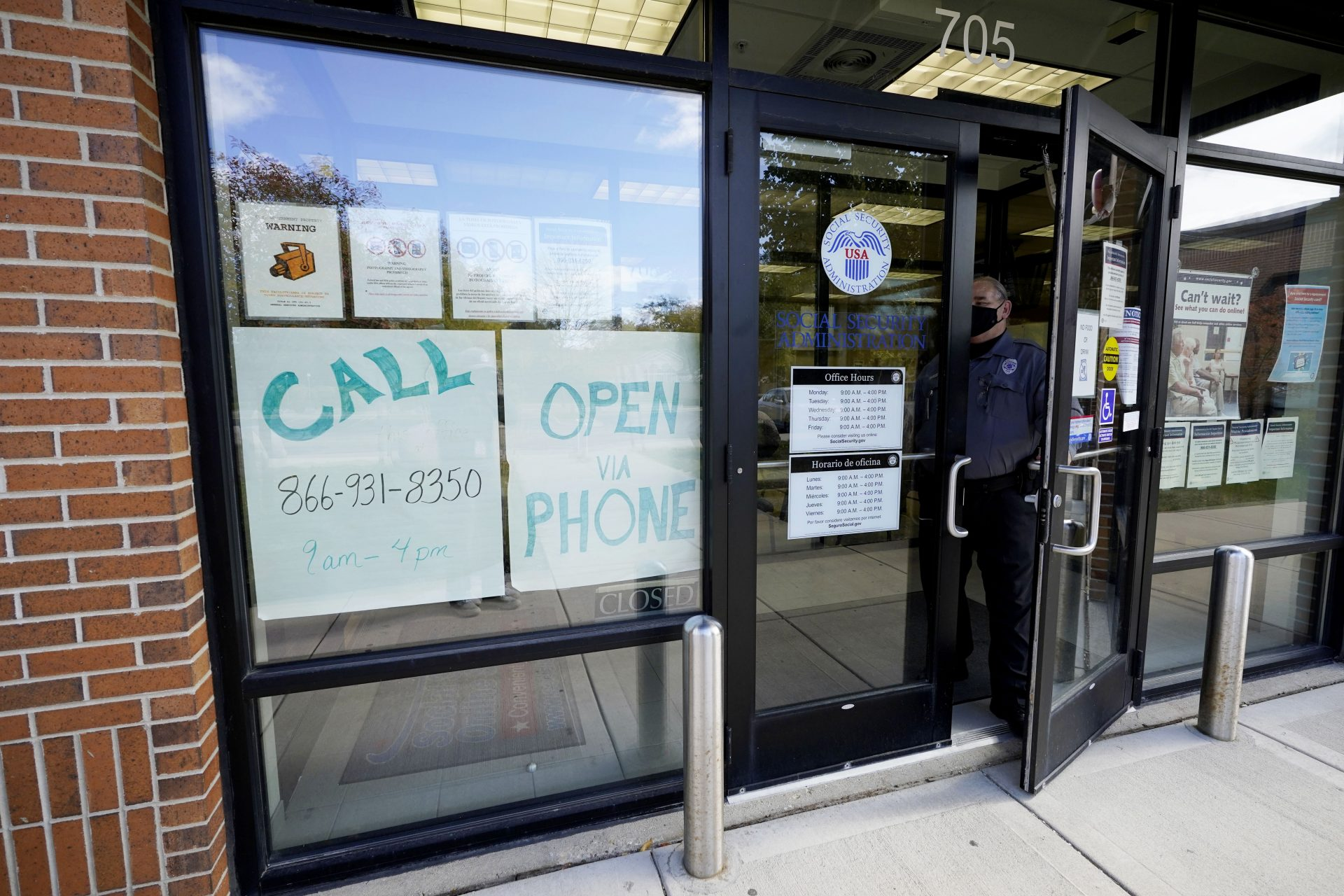 Information signs are displayed as a security guard closed a door at a U.S. Social Security Administration office in Mount Prospect, Ill., Thursday, Oct. 15, 2020. The Social Security Administration announced that retirees will get an increased Social Security benefit in 2021.