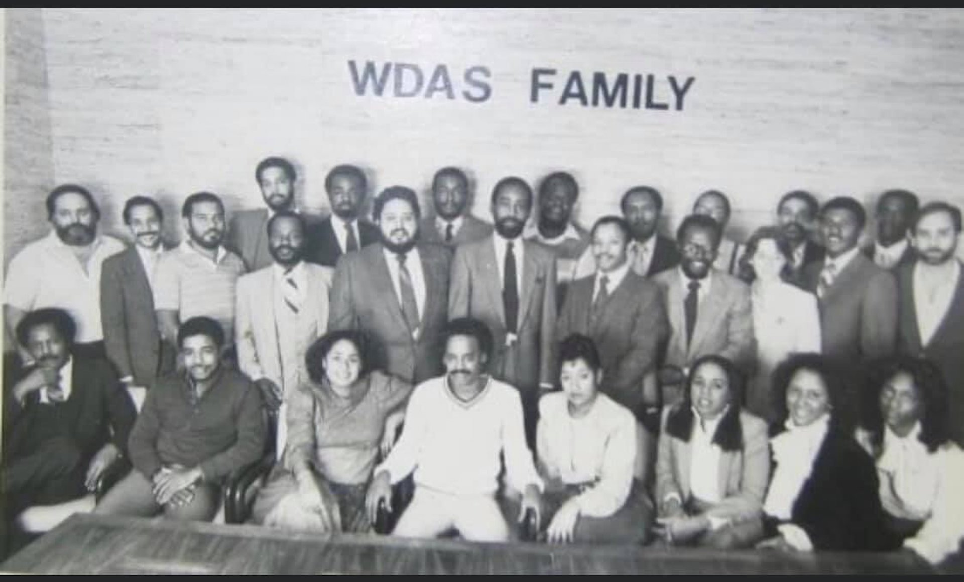 In this archival photo at WDAS, Tony Brown sits in the front row fourth from the left with Dyana Williams to his immediate left. Cody Anderson stands immediately behind Brown. Jerry Wells sits third from the right.