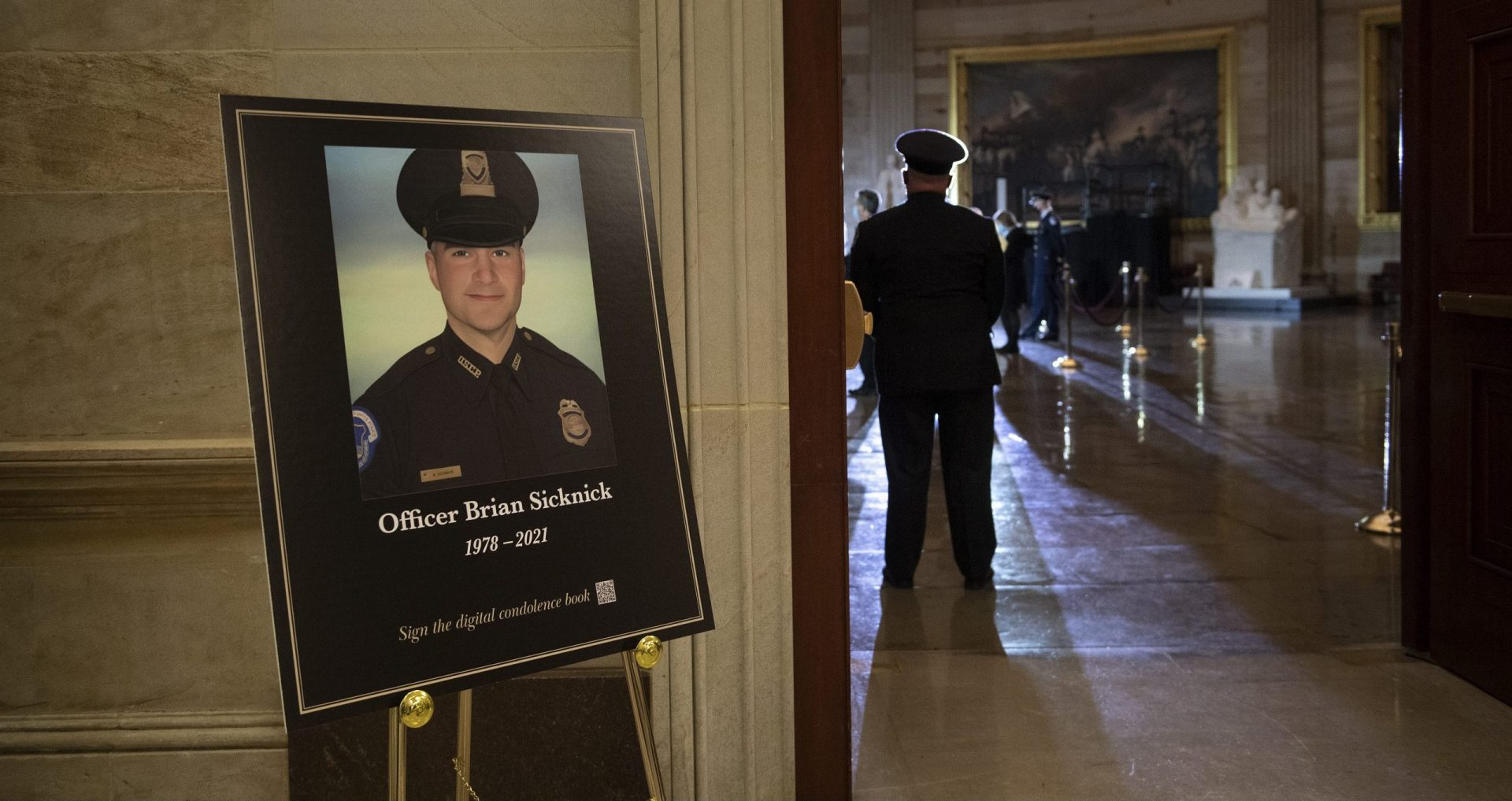 In this Feb. 2, 2021, file photo a placard is displayed with an image of the late U.S. Capitol Police officer Brian Sicknick on it as people wait for an urn with his cremated remains to be carried into the U.S. Capitol to lie in honor in the Capitol Rotunda in Washington.