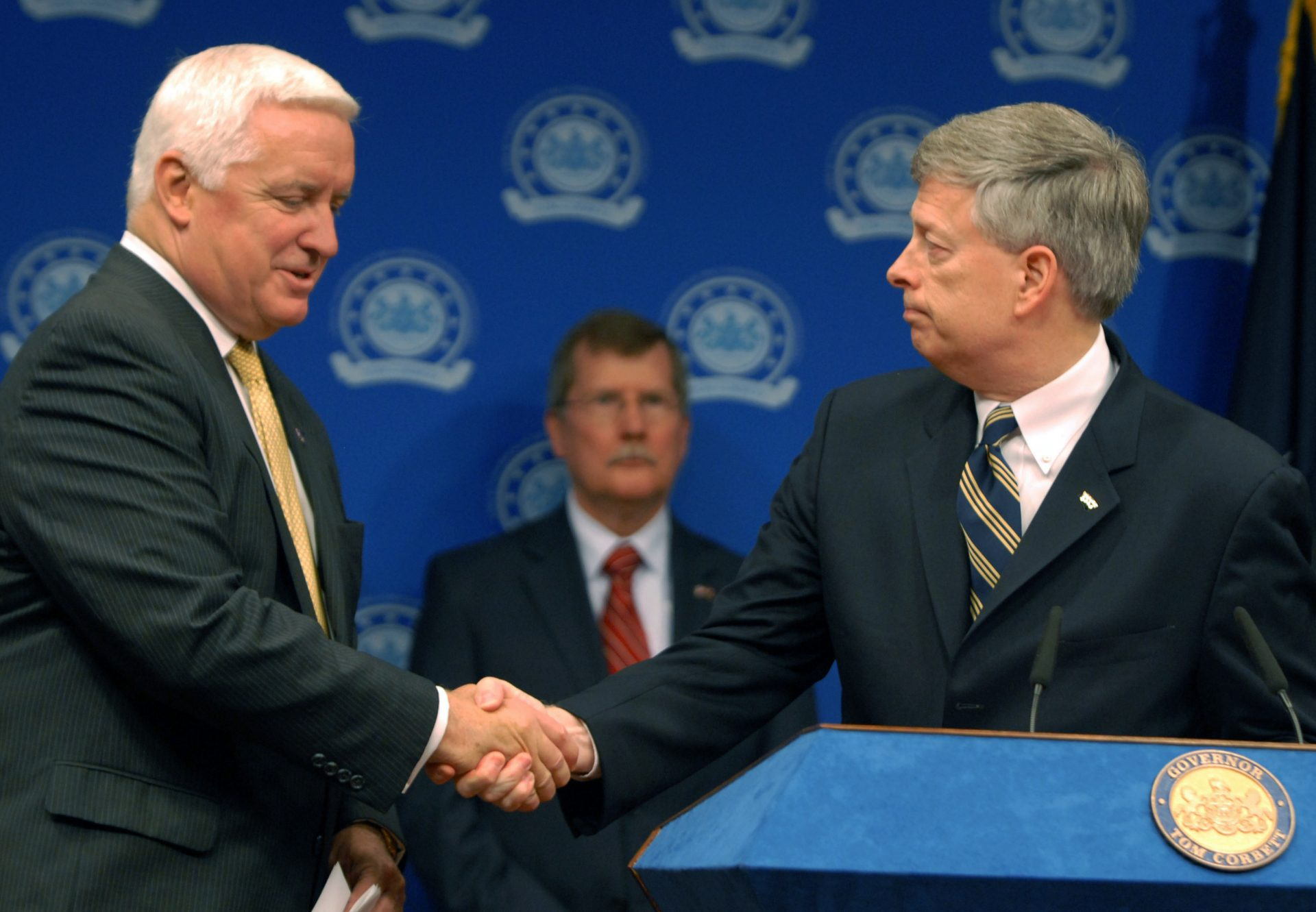 Pennsylvania Gov. Tom Corbett, left, shakes hands with Pittsburgh Chancellor Mark Nordenerg, right, at a news conference Friday, June 29, 2012 in Harrisburg, Pa.