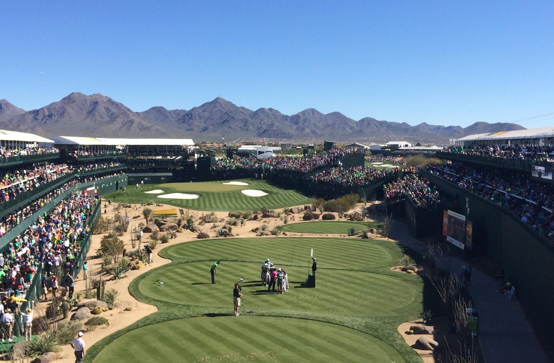In this Saturday, Feb. 5, 2016, photo, golfers and caddies gather on the 16th green during the third round of the  Phoenix Open golf tournament at TPC Scottsdale in Scottsdale, Ariz.